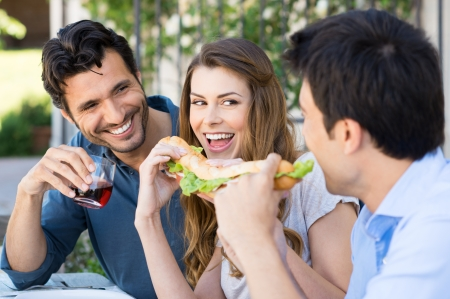 adult sandwich: Happy Group Of Friends Eating Sandwich With Fun Outdoor