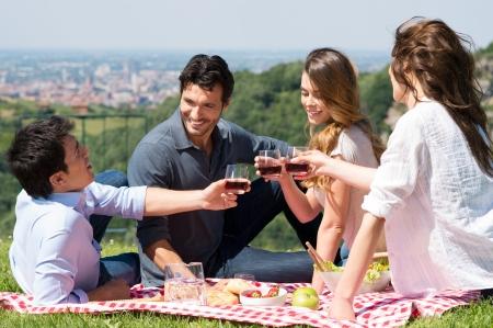 tomando vino: Feliz j�venes amigos tostado Wine Glass