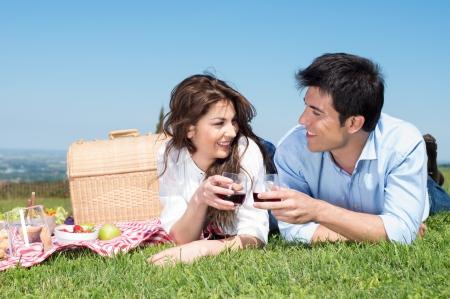행복한 젊은 부부는 잔디에 누워 와인을 즐기는의 초상화 스톡 콘텐츠