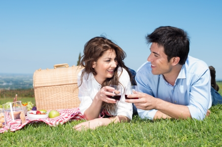pic nic: Portrait Of Happy Young Couple Lying On Grass And Enjoying Wine