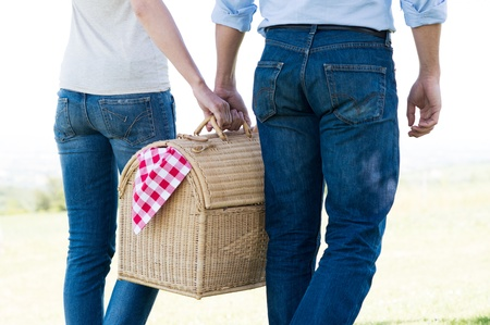pic: Young Couple Walking Holding Picnic Basket Together