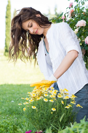 gardening gloves: Portrait Of Happy Woman Pruning Flower Outdoor in the Garden Stock Photo