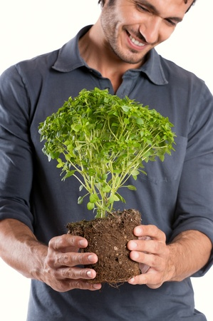 Portrait Of Happy Young Man Holding Plant Isolated On White Background photo