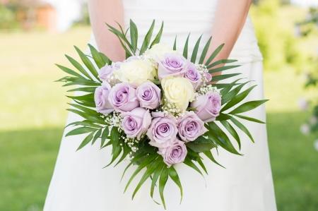 美しいバラの花束を保持している花嫁のクローズ アップ 写真素材