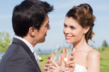 Happy Beautiful Couple Drinking Champagne To Celebrate photo