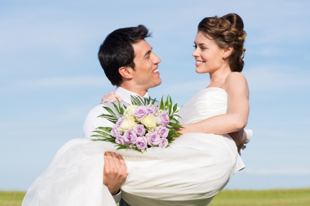 man carrying woman: Happy Young Man Carrying Her Wife During Their Wedding Day Stock Photo