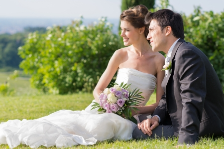 Portrait Of Happy Married Young Couple Sitting On The Grass