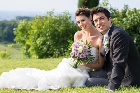 свадебный: Портрет счастливой супружеской молодые сидят на траве Фото со стока