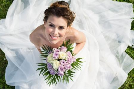 草の上に座って美しい幸せな花嫁の高いビューの肖像画 写真素材