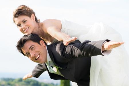 결혼식에서 자신의 신부에 피기 백 탐을주는 행복 신랑 스톡 콘텐츠