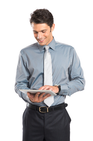 businessman standing: Happy Young Businessman Using Digital Tablet Isolated On White Background