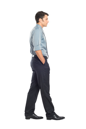 persona: Retrato del hombre de negocios joven caminando con la mano en el bolsillo aislado en el fondo blanco Foto de archivo
