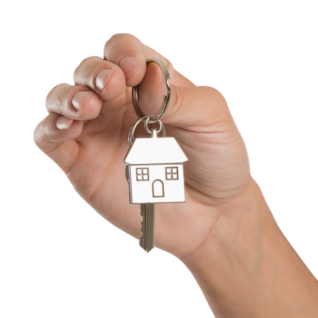 Close-up Of Hand Holding House Key Isolated On White Background photo
