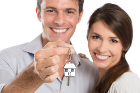 흰색 배경에 고립 된 그들의 새 집에 행복 웃는 젊은 부부 표시 키 스톡 콘텐츠