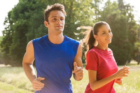 jogging in park: Healthy Young Couple Jogging In Bright Sunny Day