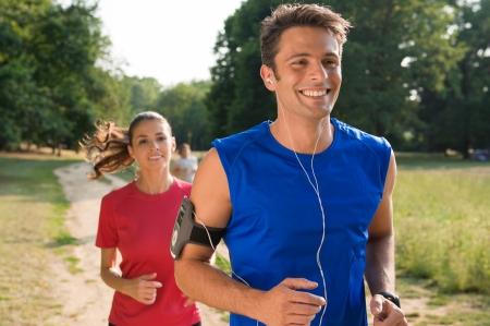 escucha activa: Hombre joven que escucha la m�sica, salir a correr con la mujer Foto de archivo