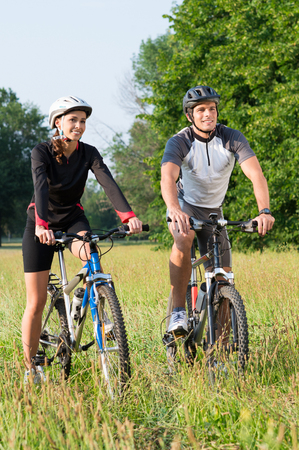 Happy Young Sportive Man And Woman On Bicycle photo