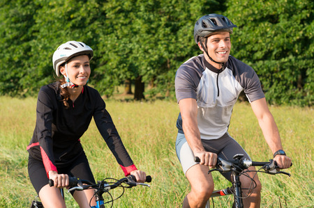 Happy Sportive Man And Woman Riding Bicycle In Meadow Stock Photo - 22583741