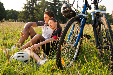 Relaxed Young Couple Sitting In Meadow Near Bicycles photo