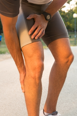 piernas hombre: Atleta de sexo masculino que sufre de dolor en la pierna en el ejercicio de