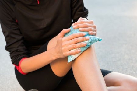 Female Athlete Sitting On Ground And Taking Treatment For Knee Pain Stock Photo
