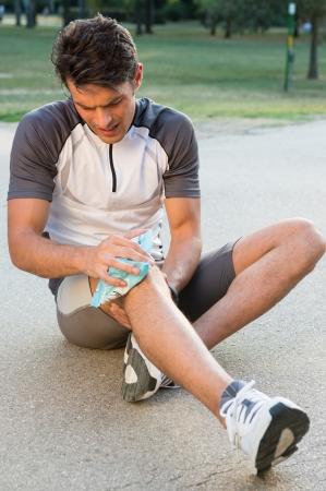 Joven Atleta hombre sentado en el suelo y tomando hielo para el dolor de rodilla Foto de archivo - 22583753