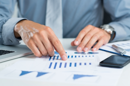 Close Up Of Graphs And Charts Analyzed By Businessman photo