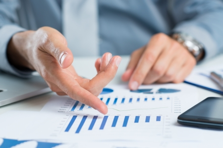 Close Up Of A Businessman At Desk Analyzing Business Graph photo