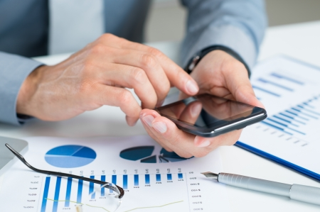 Businessman Using A Mobile Phone On An Office Desk photo