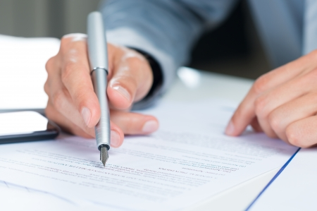 Close Up Of A Businessman Holding Pen On A Document Stock Photo