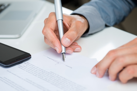 subscribing: Close Up Of A Businessman Signing Legal Documents At Desk