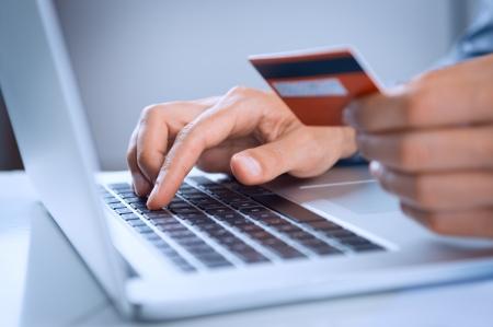 クレジット カードでノート パソコンを使用してオンライン ショッピングの男のクローズ アップ 写真素材