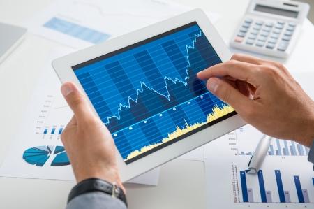 닫기 디지털 태블릿에 그래프를 분석하는 사업가의 최대