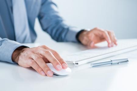 オフィスのデスクにコンピューターを使用して実業家のクローズ アップ