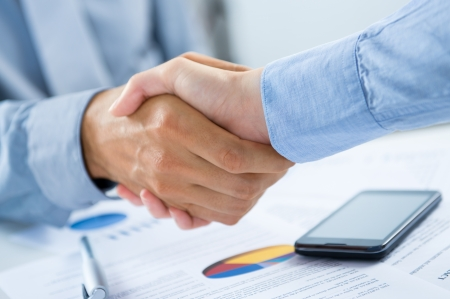 accord: Close Up Of Businesspeople Shaking Hands At Desk