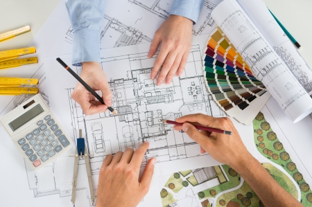 engineering: Close Up Of Two Architects Discussing Plan Together At Desk With Blueprint
