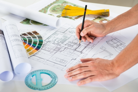 construction draftsman: Close Up Of A Male Architect Drawing Plan Over Blueprints At Desk