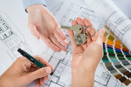 construction draftsman: Person Gives A Key To Another Person With Blueprint Below