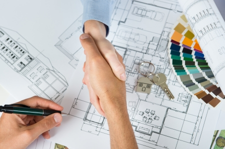 construction draftsman: Elevated View Of Two People Shaking Hand With Blueprint Below Stock Photo