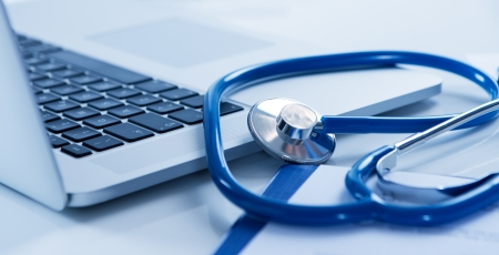 Close Up Of Laptop And Stethoscope On Desk photo