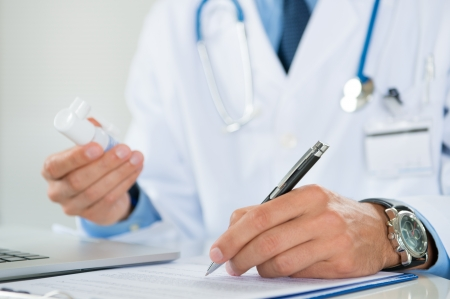 doctor writing: Close Up Of A Male Doctor Writing Prescription With Medicine In Hand