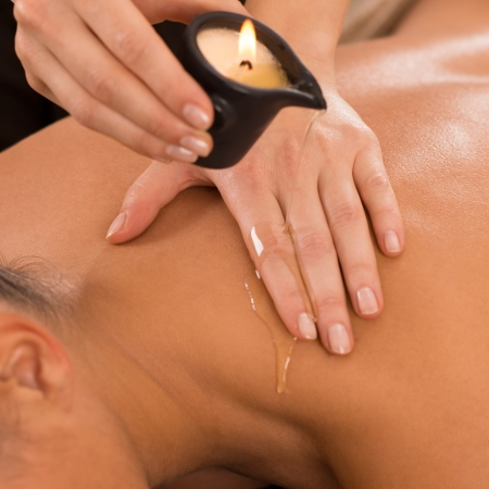 Close Up Of A Young Woman Receiving Shoulder Candle Massage At Spa  photo