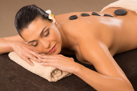 hot stone: Beautiful Woman Receiving Hot Stone Therapy Stock Photo