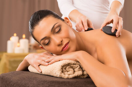 Beautiful Young Woman Receiving Hot Stones Massage At Day Spa photo