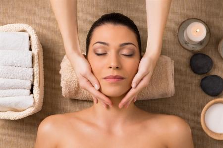 tratamiento facial: Mujer latina hermosa que consigue masaje facial en el balneario Foto de archivo
