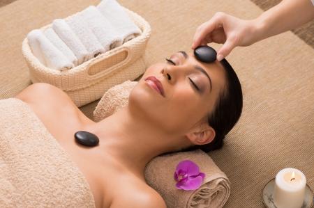 tratamiento facial: Hermosa mujer recibe un masaje con piedras calientes en su cara en un spa