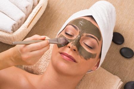 ansikts: Närbild på en kosmetolog Vem Apllies Den ansiktsbehandling till en vacker kvinna In Day Spa Stockfoto