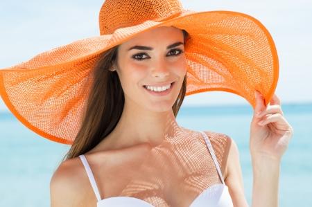 Porträt der lächelnden Mädchen In Orange-Hut am Strand Standard-Bild - 25271535
