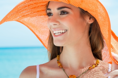 Portrait Of A Girl At Beach With Orange Hat photo