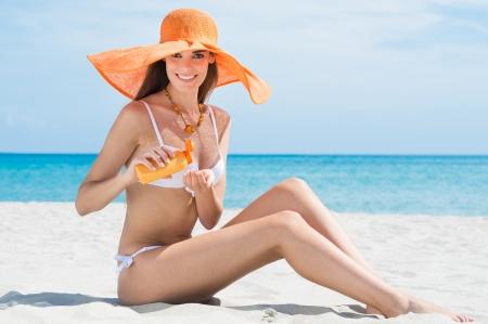 Happy Young Woman In Bikini At Beach Applying Moisturizer photo
